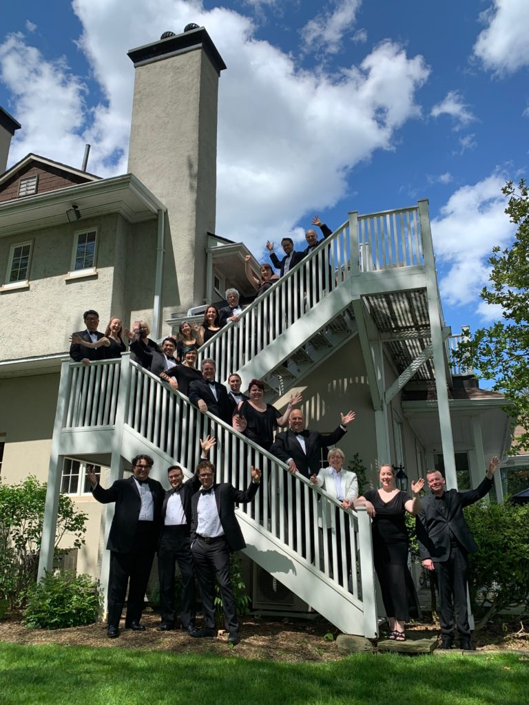 Elmer Iseler Singers waving on a staircase at the Toronto Hunt Club